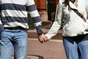 A young couple out for a stroll holds hands on a sunny springtime Saturday as they cross a street in downtown Doylestown PA.